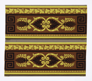 Two borders printed side by side on the length of paper. Central motif is a mirror image of a modified scissors scroll decorated with elements derived from pineapple, bay and palm leaf. This motif is enclosed by black lines ending in Greek Key patterns. Above is a string of leaves, below, a band of grape leaves. Yellow and black on chocolate ground.