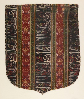 Shield-shaped cope hood, striped vertically with broad stripes of dark blue containing Arabic inscriptions in white, red and yellow, alternating with narrower stripes of red with conventionalized floral and foliate motifs in dark blue, yellow, green and white. The blue and red stripes are separated from each other by narrow stripes of green with a geometric knot-like design in red and yellow. These stripes are bordered with very narrow stripes of white, yellow, red and dark blue.