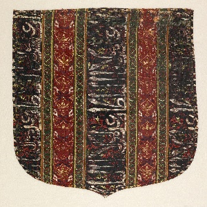 """Shield-shaped cope hood, striped vertically with broad stripes of dark blue containing Arabic inscriptions in white, red and yellow, alternating with narrower stripes of red with conventionalized floral and foliate motifs in dark blue, yellow, green and white. The blue and red stripes are separated from each other by narrow stripes of green with a geometric knot-like design in red and yellow. These stripes are bordered with very narrow stripes of white, yellow, red and dark blue. The Arabic inscription is translated as """"Glory to our master the Sultan."""""""