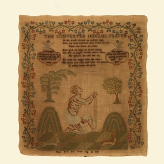 An embroidered sampler with a scene of two mountains with rivers flowing from them. A figure in chains and a simple loin cloth kneels between them, with his hands raised in prayer. Above, a verse is flanked by two medallions supported by angels. With a floral border on three sides.  The verse reads:   The Converted Indian's Prayer  In de dark wood no indian nigh Den me look heaven and send up cry Upon my knee so low Dat god so high in shiny place See me nigh with teary face My priest do tell me so He send his angels take me care He come his self and hear my prayer If indian heare do pray  Within the medallions:  The angels of the lord bless ye the lord praise him and magnify him for ever  and  The angel of the lord cried loud saying prepare to meet thy god