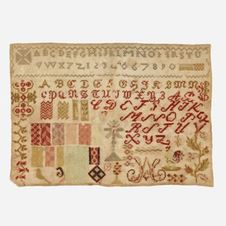Alphabets, numerals, and a number of designs for darning and floral patterns worked in colored wools on brown canvas.
