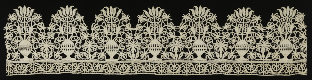 Deeply scalloped border with a vase of flowers in each scallop. Narrow bobbin lace in flower pattern joined to straight edge of border.