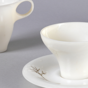 White plastic cup with tapered bottom and wide mouth, applied circular handle with thumb piece. White saucer with twig or vegetal stem painted on.