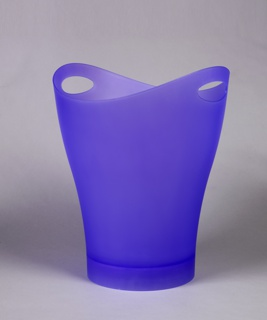 Large frosty-lavender trash can; oval mouth pierced on either side with holes for hand grips, tapering to circular base.