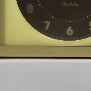 Ivory plastic half semicircle, dark burgundy face with white lettering and time pointers, brass plated base and metal back plate in grey.