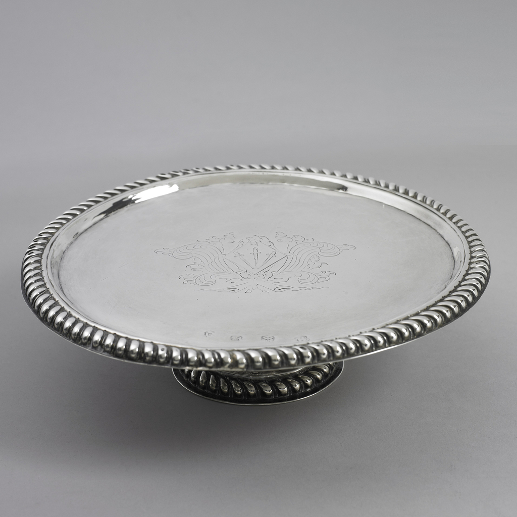 """Cylindrical foot, straight platter. Spreading base of foot and rim of top edged with repoussé cording. Engraved in center are three swords in lozenge shield, surrounded by feathers. """"M.P."""" engraved on back."""