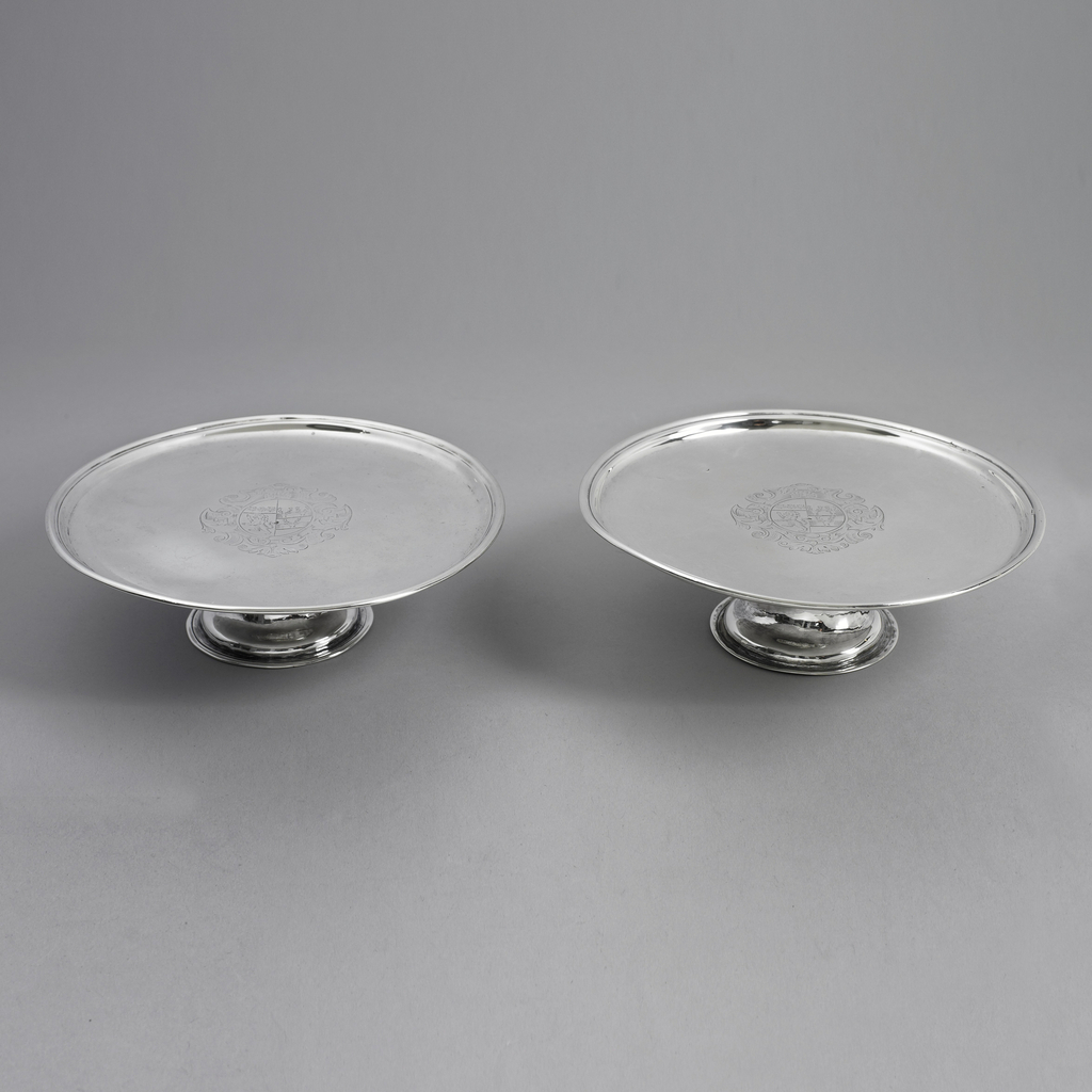 Both salvers: slightly concave foot, spreading at bottom, ending in flat rim. Flat top with molded rim. Engraved in center circular-oval shield, three roses, lion rampant, three heads of stags. Scrolled framing. Inscribed on back.