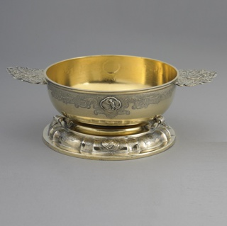Lobed oval, on scrolled feet, with four-lobed relief medallions of the Four Continents; engraved decoration.