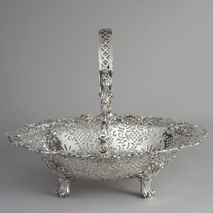 George II cake basket. Oval basket ajoure with rosetted trelliswork and foliate devices, the rim applied with grape clusters and wheat ears; the hinged bail handle with enleafed scrolls and female busts; on scroll feet headed with a frilled shell.
