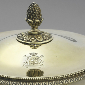 Footed urn-shaped gilt bowl with mascaron handle on each side. Neck has band of large vertical granules. Foot with band of small granules and leaf motif. Everted lip decorated with same band, upon which rests lid with granulation border and artichoke finial. On lid, engraved coat of arms: two dogs holding crowned shield.
