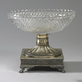 Oval glass bowl, exterior cut with allover diaper pattern; smooth interior. Bowl stands on flared foot in gilt silver, decorated with blossoms and elongated petals, resting on rectangular footed stand with four lions' feet; sides with foliage motifs.