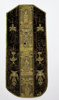 Back of a chasuble with an embroidered orphrey band down the center, embroidered motifs at the sides, and bound all around with gold braid. The deep brown velvet side panels are embroidered in gold metallic and polychrome silks with angels on orbs and floral arrangements. The center band is densely embroidered with four saints in different architectural niches.