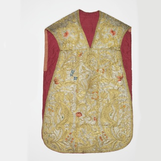 Chasuble of white silk entirely covered with embroidery in gold and silver metallic yarns and multi-colored silk floss, backed with white linen and lined with red silk. Background of couched silver, with ornamental foliage in couched gold thread and naturalistic flowers in colored silk floss.