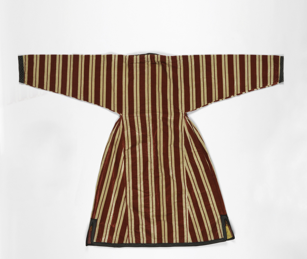Red and white striped velveteen robe with a full skirt pleated into a narrow waist and deep set sleeves narrowing to the wrist. Edged with black cotton twill that is machine stitched in light blue and white. Lined with printed cotton with stripes and polka dots in red, green and yellow. Facings of silk warp ikat.