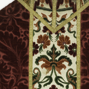 Complete chasuble of red figured velvet with woven orphrey bands of a different velvet, edged all around all areas with gold metallic ribbon.The side panels are of red cut and uncut velvet in a satin foundation in a large-scale scrolling floral design. The orphrey bands are of cut and uncut velvet in reds, pinks and greens on a white satin ground in a large-scale, symmetrical floral design. Lined with linen.