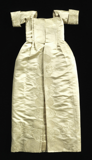 Dress of white satin; pleated bodice; square neck, elbow sleeve with wide cuff turned back; skirt opening to show panel; embroidery on cuffs, front opening and hem in design of flowering sprays and sections filled with ornamental stitches; lined with white silk.