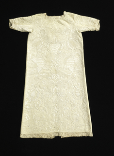 Dress or coat cut without fullness. Has opening from neck to bottom and long sleeves. Foundation 2 & 2 twill weave nearly covered with white linen embroidery (using satin, overcast cord, back, herringbone, laid work, coral, knot, buttonhole, and detached chain stitches) in design of flowers, leaves, and fruit worked solidly in ornamental stitches. Binche lace sewed in neck at bottom of sleeves and of dress.