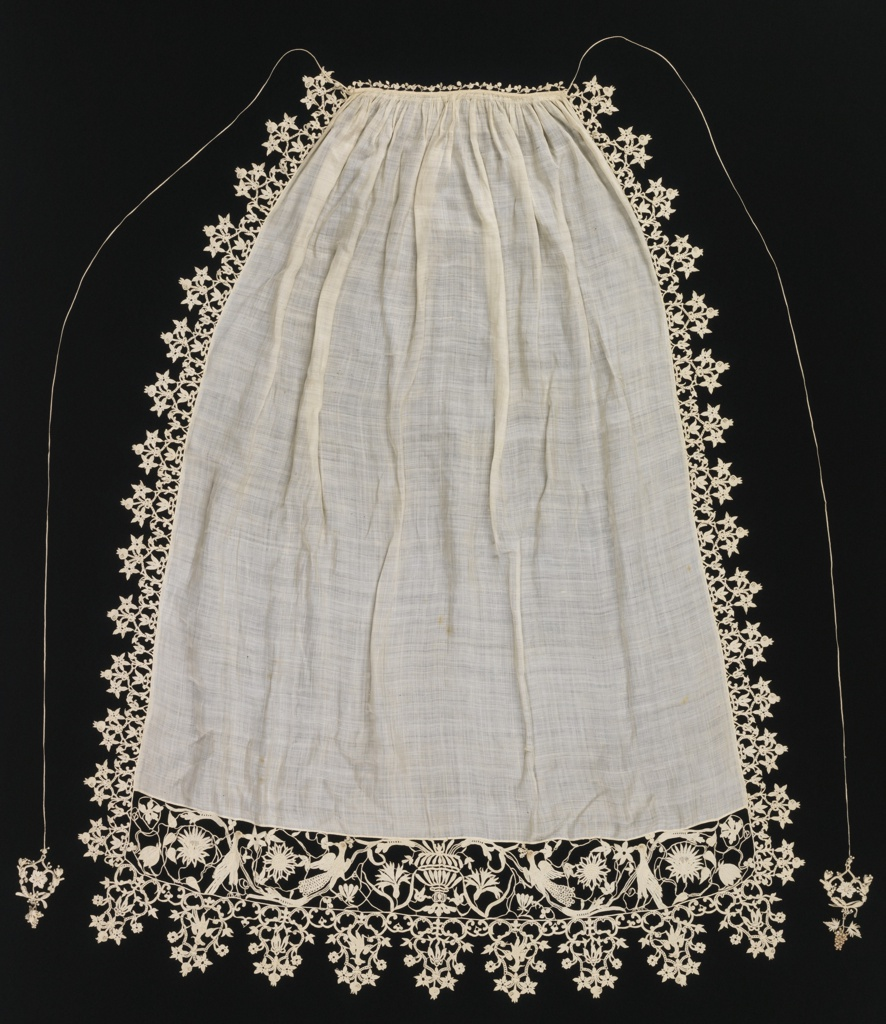 Long apron of fine white linen trimmed at sides and bottom with border of needle lace. Gathered at top into narrow band, finished with minute leaves of the same; long cords of lace ending in tassels of needle lace. Design of bottom border shows central vase flanked by birds. Floral borders at side.