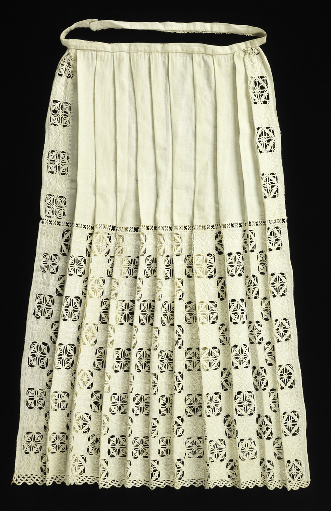 White linen apron pleated into a narrow band at the top. The sides and lower half of the apron are decorated with squares of cut work with needle-lace fillings alternating with squares embroidered in white in a stylized plant motif. The bottom is trimmed with scalloped needle lace.