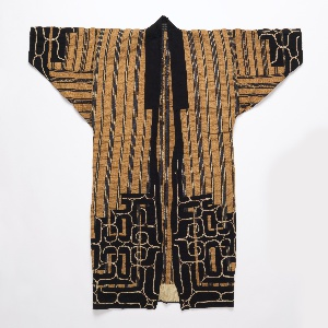 Robe made from narrow widths of cloth woven from elm bark, in tobacco brown with varied stripes of dark indigo blue and white. Dark blue cotton appliqué with white couched-thread embroidery adorns the hemline, sleeve cuffs, and upper back. Dark blue cotton neckband.