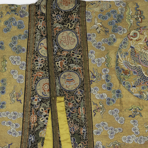 "Robe in the form of a large rectangle composed of widths of fabric which are continuous from the front hem over the shoulder to the back hem. The garment is open down the center front, and the front borders are continuous with the neck band. The borders on the outside edges are also continuous over the arm, and have openings for the hands.  Each front panel contains two medallions with a full-face dragon chasing a magic pearl in the sky above a mountain.  On the back, in the upper center is a large medallion with the ""sacred Pagoda"" (Lamaist) plus two small medallions, one with a representation of the sun, the other the moon. Below are two large medallions each with a profile dragon chasing a magic pearl in the sky above a mountain. These three large medallions on the back are placed above mountains raising out of a foaming sea. The entire field of the front and back panels is filled with clouds, auspicious symbols, and bats carring symbols. The background is metallic gold with the pattern in colored silks. The vertical borders on the front and back contain medallions with the 8 Buddhist Emblems in colors on a black background. The bottom bands on front and back have dragons raising out of the sea, medallions containing either a carp, turtle with snake, or Ch'i-lins, plus other auspicious symbols in colors on a black background.  Many of the popular and commonly used Chinese symbols are used including the 8 Buddhist emblems, those of the Taoist Immortals, 12 Imperial, and 100 Antiques.  The entire pattern is embroidered, as is the background on the front and back panels (the background of the borders and bands is the foundation fabric). The entire robe is lined with silk 8-harness satin damask with an all-over pattern of clouds (Ming type) in greenish-yellow and tan. There are two embroidered yellow silk pointed tabs and one button with loop on the edge of the opening."