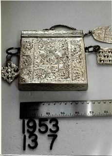 Tall rectangular box with domed sliding cover, with ring in center from which a hand-shaped pendant is suspended on a chain. On sides, two lozenge-shaped pendants suspended from rings. Entire box decorated with crudely engraved flowers and scrolls, surrounding eight-lobed strapknot. Illegible mark.