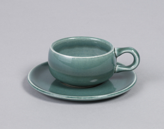 Bulbous demitasse and saucer. Cup with c-shaped handle, saucer with slightly curved edge and impression for cup.