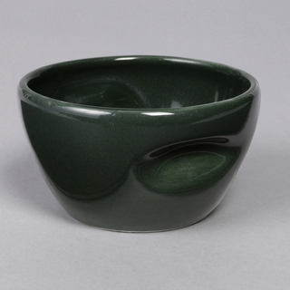 "Squat tapering circular form with circular mouth and two indentations in wall; ""spruce"" green glaze."