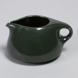 "Squat globular form with ovoid mouth, short pinched spout and circular loop handle; ""spruce"" green glaze."