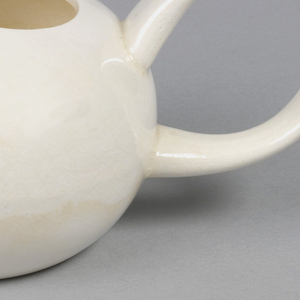 White cream boat with large loop handle and elongated spout.
