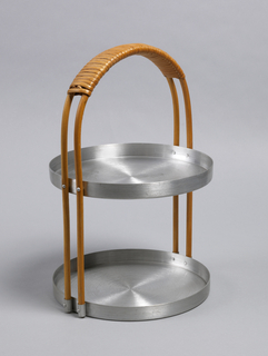 Double-tiered circular tray stand with rattan-wrapped handle connecting to each tray and forming semi-circular carry support.