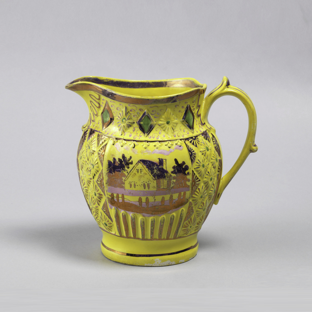 Yellow pitcher with embossed with pink lustre decoration, curved spout and loop handle with feathered treatment. Depiction of house in a landscape surrounded embossed floral diamond pattern.