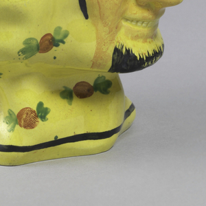 Mask of smiling satyr with black beard; rest of mug has round protrusions decorated with painted red berries with green leaves on yellow. Large, open spout, black line at rim and base. Angular and curved handle.