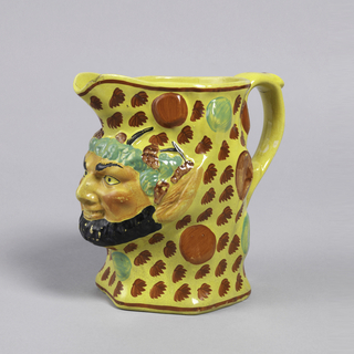 Satyr mask with black beard with pointed ears and green hair projects out of jug. The rest of jug is decorated with red leaves and circles on yellow ground. Open spout; red border around rim and base.