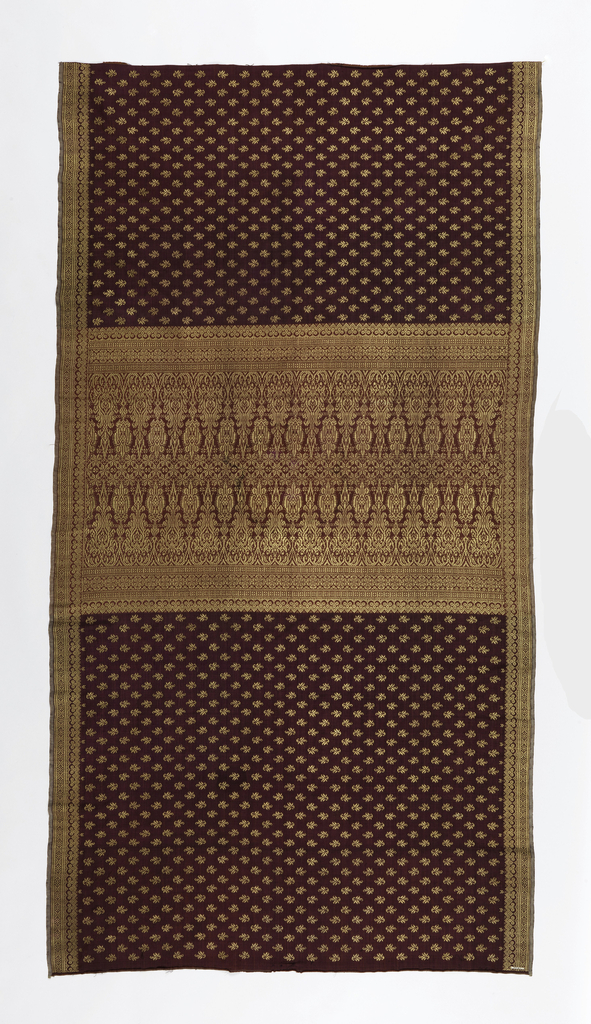 "Brocaded sarong (kain songket) with a maroon silk warp and purple silk weft, brocaded with an all-over repeating leaf pattern in gold thread. Geometric borders brocaded in gold and a wide center band heavily brocaded in gold in the stylized ""lawi ayam"" or 'cockerel's tail feathers' motif."