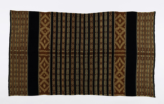 Rectangular panel made up of two lengths of cloth stitched together. Design of wide and grouped narrow stripes, in indigo blue and red. The red stripes are patterned in warp ikat with geometric and floral forms reserved in white. The seven narrow black stripes on each skirt half are associated with the Greater Blossom or 'hubi ae' ancestral group.