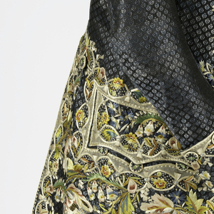 Man's coat of blue and black patterned silk with large-scale floral embroidery in polychrome silks with appliqué of silk and silk net. Deep borders of embroidery at the center front edges, back vent, pocket flaps and sleeve cuffs. With matching covered buttons; modern machine-lace at cuffs. Lined with white silk twill.