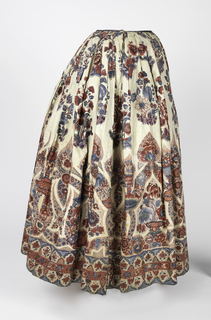 Petticoat of glazed chintz with a deep decorative border at the bottom in blue, violet, and shades of red on a white ground. The design is arranged to fit the bottom of the petticoat, and consists of a series of pointed arches made up of floral bands, rising to sharply pointed ovals of blossoms. Between points of arches appear jars of flowers. The arched spaces frame, alternately, clusters of various blooms, or crossed, sharply pointed curved flower bands.The bottom of the skirt is finished by a border 5 3/4 inches wide of small arches, reversed top and bottom, in blues, with red flowers on dotted red ground; intersected by a red band with floral decoration in blue or reserved in white.The painting of the arches is elaborate and a feathery effect is produced by a background of minute foliage forms in red, or dotted grounds of red, or feathery detail in black. In the open space above the border are detached sprays of natural size flowers, including tulips and roses.   Lined with stiff white linen; one seam. At top set into waistband of green twill tape with tie cords at the side. The fabric was made in India, the petticoat was made in Europe, probably in The Netherlands.
