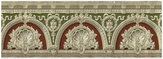 Flitter frieze with classically-styled motifs. Contains large scallop shells within half-circle deep red niches. Architectural molding with dentils along top edge.  Egg and dart molding around niches. Molding along bottom edge with beading. A laurel wreath and ribbon with bowknot occupies the space between the niches. Printed in deep red, green and grisaille, with gold mica flake highlights.