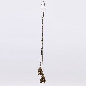 Lond cord of metallic thread terminating at each end in a ball-shaped tassel, curled, looped and heavily studded with pailettes and glass stones.