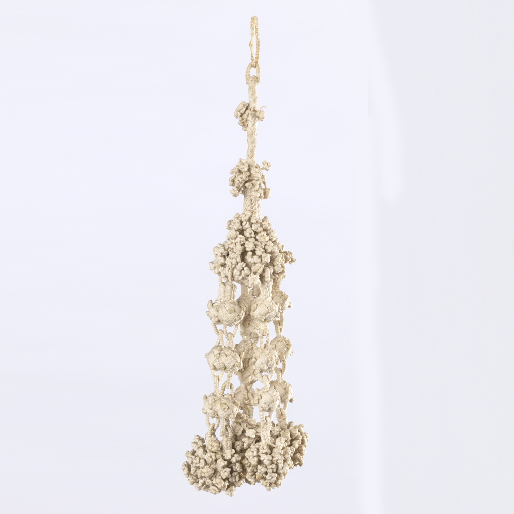 White tassel of braided and knotted linen. A braided cord descends to an upper ball, from which hang six pendant elements of three braided balls each, terminating in clusters of knotting.