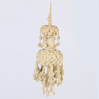 Knotted white linen tassel with human figures decorated with coiled metal wire and hammered metal sequins.