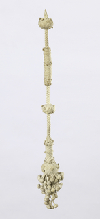 Linen tassel, braided and knotted. Long stem, braided and in parts knotted terminating in pear-shaped unit to which are attached two double balls. Bottom of pear-shaped unit and double balls covered with small knotted balls.