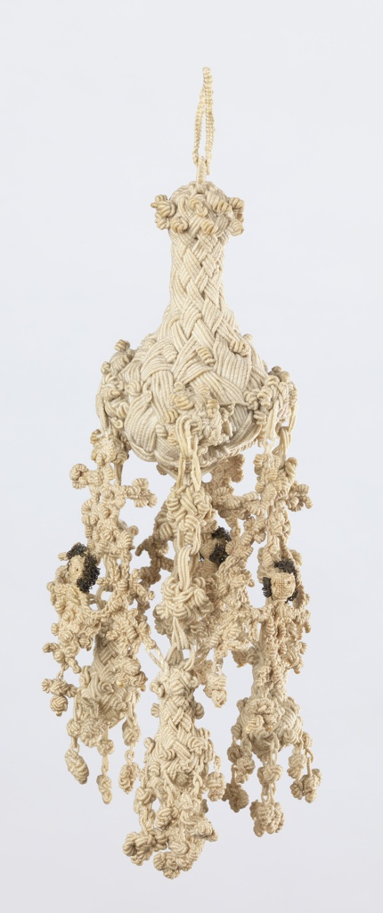 Linen tassel, braided and knotted. Double loops attached to pear-shaped unit from which hang three elaborate knottings connected with one another in shape of human figures. Hair of figures made of tarnished metal wire. Suspended center element.