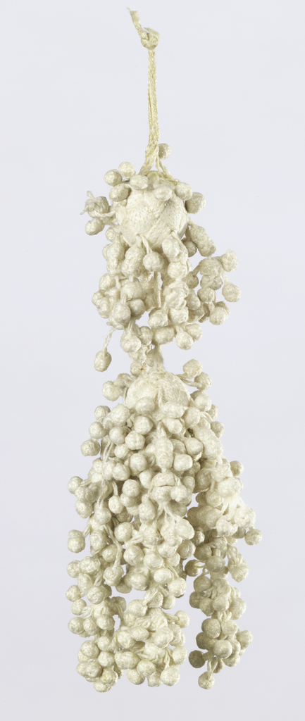 White linen tassel with one circular base attached to attached to a slightly larger, pear-shaped base (hanging below). Cores are braided over with linen yarns worked in groups for a basket-weave effect. Around the bases hang tiny braided balls and from the bottom of the pear-shaped base hang a few longer clusters of the tiny braided balls.