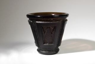 Vase of thick brown glass in shape of truncated cone with widest diameter at mouth; rounded lip and foot; around body are four acid-etched and carved slightly tapered panels each with a diamond-shaped figure in center and a half diamond-shaped frame on each side.