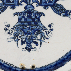Oval plaque with molded border, 2 holes at top for hanging; painted in underglaze blue on white with grotesque decoration composed of fruit, birds, mask, lambrequin; around the border with a scroll pattern covered with blue; back plain.