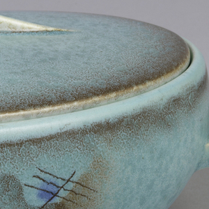 Oval lid and body.  Slightly convex lid surmounted by a backward s-shaped vertical handle about nine centimeters long. Oval body narrowing at bottom with curving and descending ramp-like handles on either narrow side.  Both pieces glazed turquoise with highlights of airbrushed brown.  Abstract surface decoration, in the center on the long side of the box, of lines, waves, and patches in airbrished royal blue, brown, and rust.
