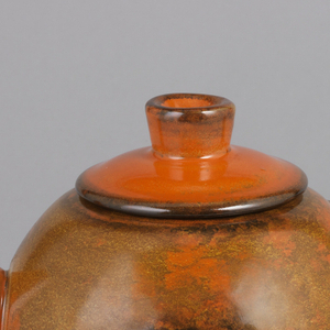 Spherical body glazed in red, orange, brown and blue with a triangular handle.