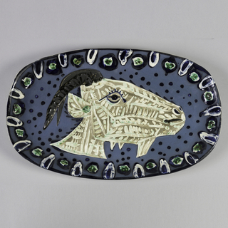 Oval plate depicting head of white and beige goat with curved horns, on blue spotted ground. Border decorated with alternating abstract forms with white highlights.
